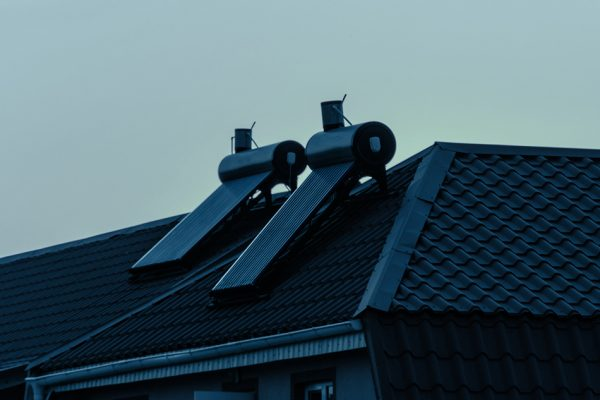 Solar water heaters on a residential house rooftop at sunset. Renewable energy for house